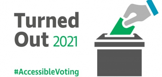 """A hand is reaching down to a ballot box with a ballot paper. On the left of the ballot box are the words, """"Turned out 2021 #AccessibleVoting."""""""