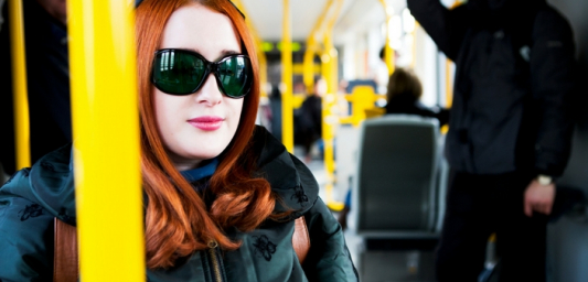 Woman with red hair and sunglasses sitting on a train