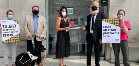 Image shows Keith Valentine, Keith's guidedog Dottie, Sophie and Roisin from the Policy and Campaigns Team and Sekha who is handing the petition to Ieysha Warner, receiving the petition on behalf of Andrew Haines (Chief Executive of Network Rail).
