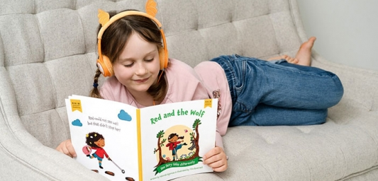 Girl reading ReadAlong's Red and the Wolf with headphones on