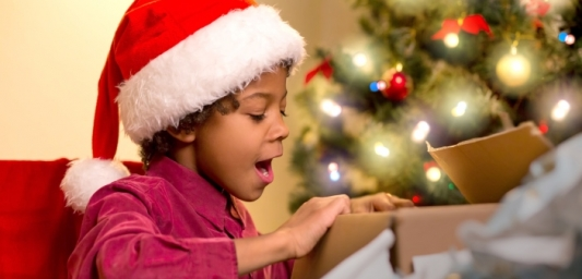 Image shows a young boy wearing a santa hat, opening presents and looking shocked and excited