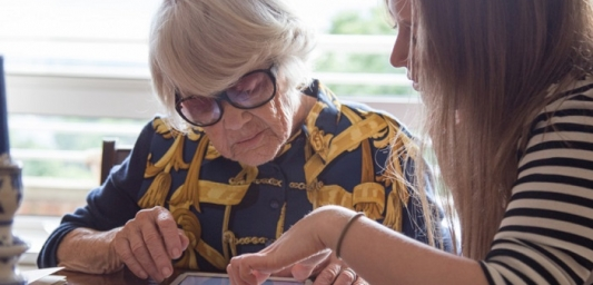 a woman helps an older lady wearing dark glasses to use an ipad