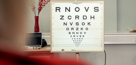 Inside an optometrist's office with an eye test chart as the focus