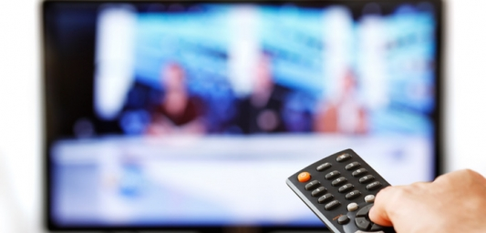 Remote control in the foreground pointing at a blurred TV screen