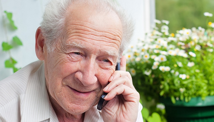 An elderly man talking on the phone