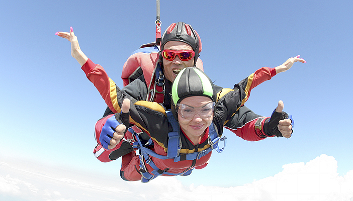 Image shows a woman harnessed to her instructor, in the air. The woman has her arms out and her instructor has his thumbs up.