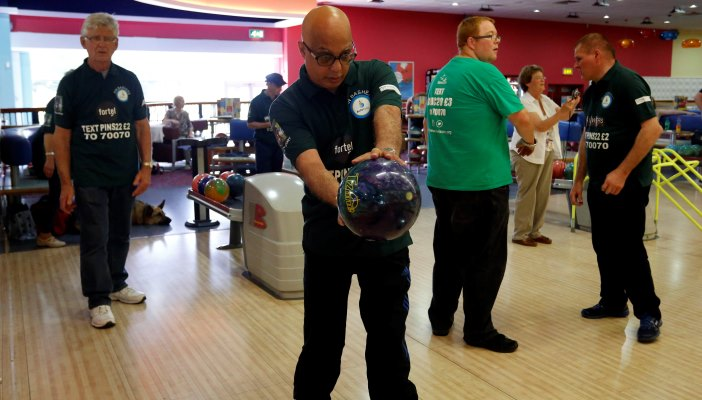Image shows Ranjit mid-bowl at a Tenpin bowling session