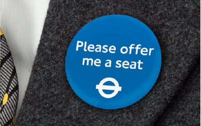 TfL Please Offer Me a Seat badge pinned on a grey jacket