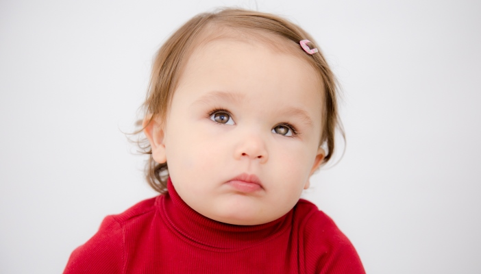 Photo of Violet looking up with a white glow in her left eye, wearing a pink clip in her hair and a red jumper