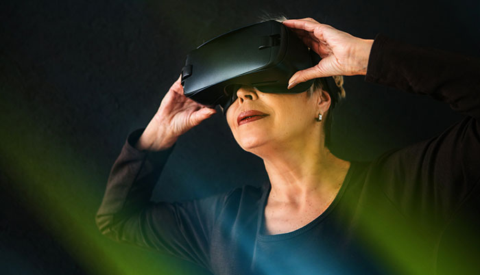 An older women wearing a virtual reality (VR) headset