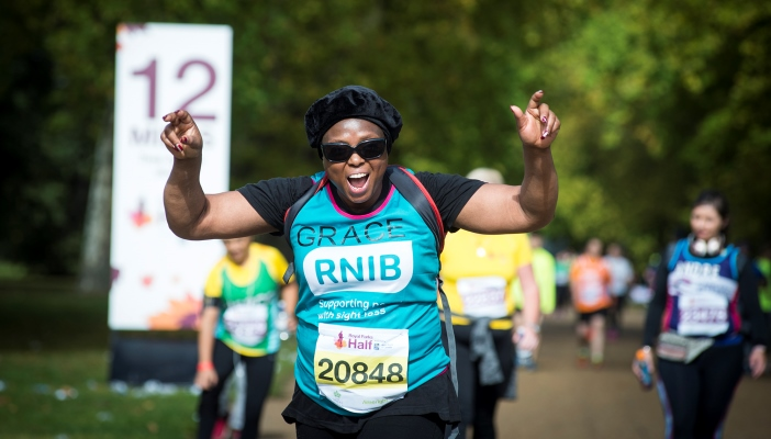 Image shows a woman running during a race, wearing an RNIB vest, with her hands up in the air and looking very happy!