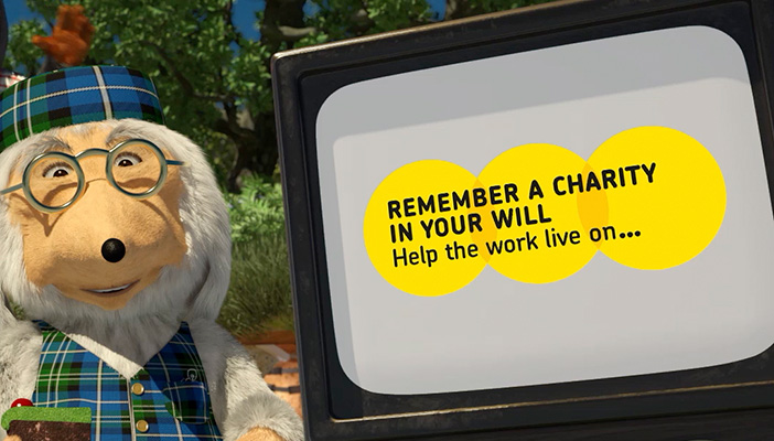 "A Womble stands next to a TV screen displaying the words ""Remember a charity in your will, help the work live on"""
